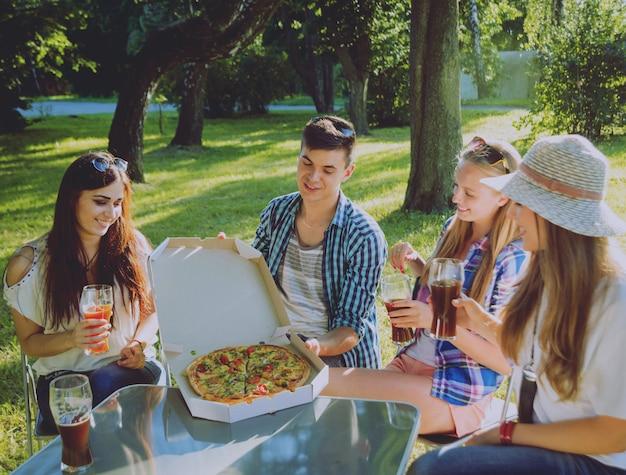 Vrolijke vrienden op picknick in het park. pizza eten