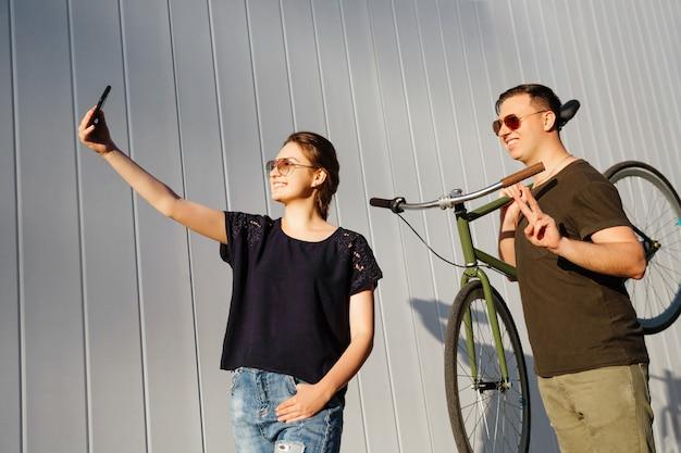 Vrolijke vrienden samen plezier. de mooie vrouw neemt een selfie op smartphone, die zich met gelukkige kerel bevindt, een fiets op zijn schouder houdt en vredesteken toont. buitenshuis.
