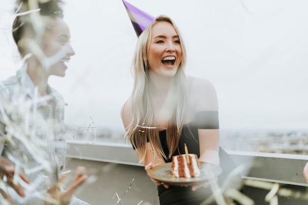 Vrolijke vrienden vieren een verjaardagsfeestje op een dak
