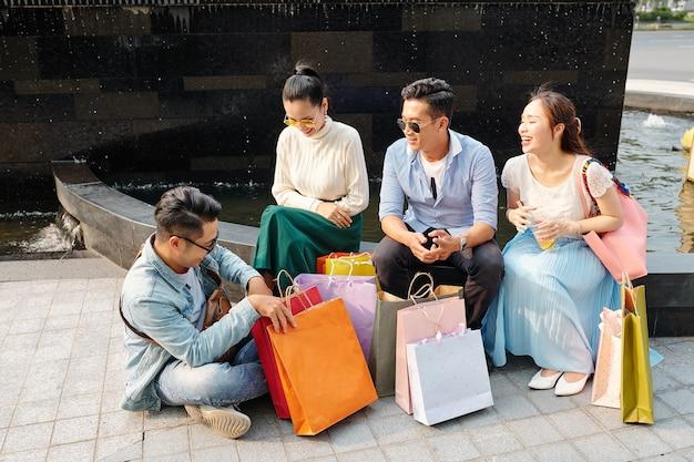 Vrolijke vrienden zitten buiten met papieren zakken in de buurt na het winkelen in het winkelcentrum