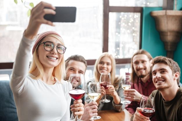 Vrolijke vrienden zitten in café en maken selfie via de telefoon.