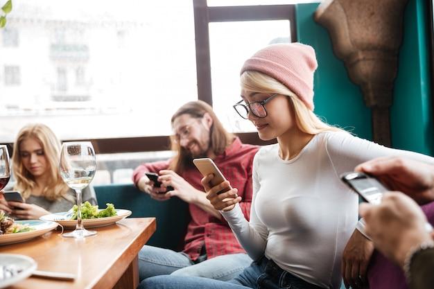 Vrolijke vrienden zitten in café met behulp van mobiele telefoons.