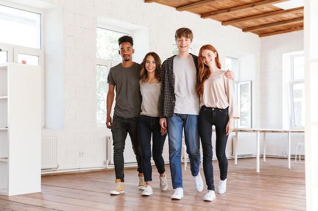 Vrolijke vriendenstudenten die in klaslokaal lopen
