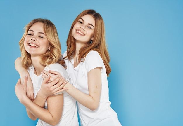 Vrolijke vriendinnen in wit t-shirt hugs emoties blauwe achtergrond. hoge kwaliteit foto