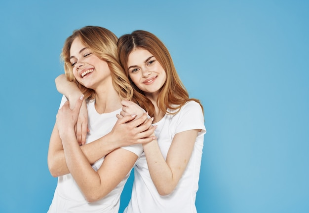 Vrolijke vriendinnen in witte t-shirt knuffels emoties blauwe achtergrond