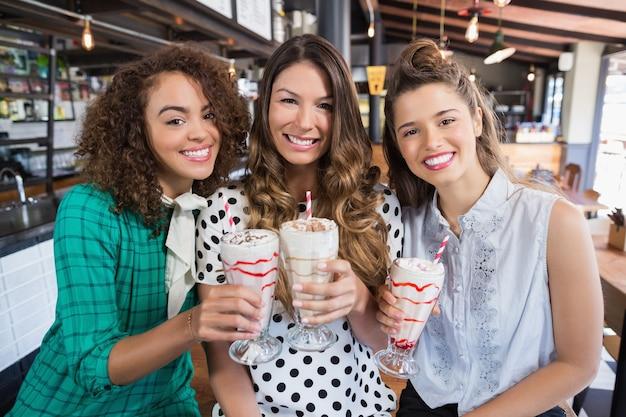 Vrolijke vriendinnen poseren met drankjes in restaurant