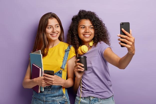 Vrolijke vriendinnen poseren met hun telefoons