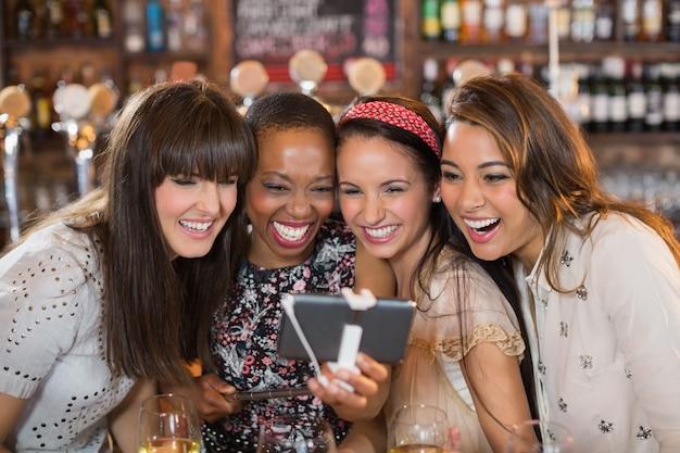Vrolijke vriendinnen selfie te nemen in de pub