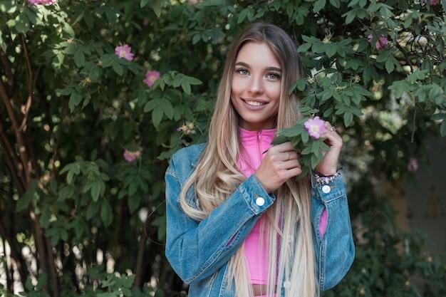 Vrolijke vrij aantrekkelijke jonge vrouw met luxueus lang haar in een spijkerjasje in een roze top staat en schattig lachend in de buurt van een groene bloeiende struik in de straat. glamour gelukkig meisje ontspant buitenshuis.