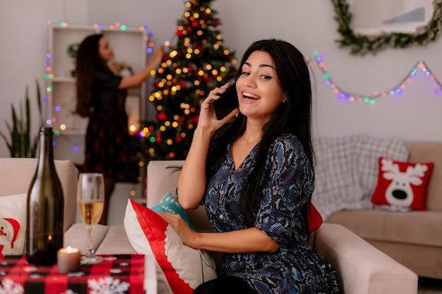 Vrolijke vrij jong meisje praat over telefoon zittend op een stoel en haar vriend versiert kerstboom genieten van kersttijd thuis