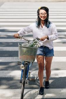 Vrolijke vrij jonge chinese vrouw met fiets die weg in stad kruist