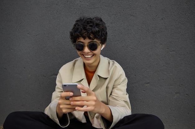 Vrolijke vrij krullend donkerharige vrouw in zonnebril trendy outfit dragen zittend op de stadsvloer in stijlvolle kleding, vreugdevol glimlachen tijdens het chatten met vrienden op haar smartphone
