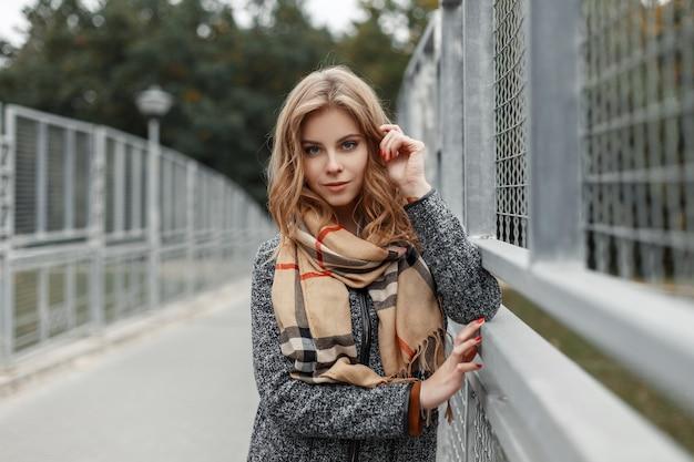 Vrolijke vrij schattige jonge vrouw in een stijlvolle vintage herfstjas in een modieuze beige sjaal staat buiten in de buurt van een vintage metalen hek