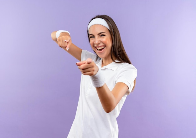 Vrolijke vrij sportieve meid met hoofdband en polsbandje doet je gebaar geïsoleerd op paarse muur