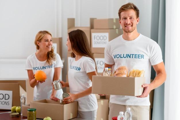 Vrolijke vrijwilligers die helpen met voorzieningen voor een goed doel
