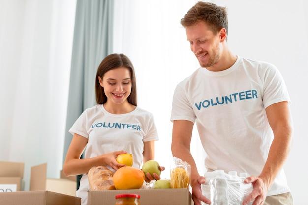 Vrolijke vrijwilligers die voedsel bereiden voor donatie