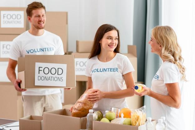 Vrolijke vrijwilligers die voedselvoorzieningen voorbereiden voor donaties