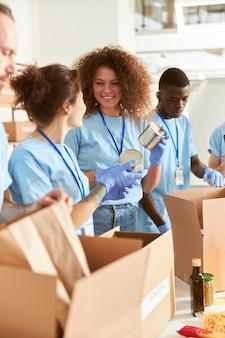 Vrolijke vrijwilligers in beschermende handschoenen die ingeblikt voedsel sorteren in kartonnen dozen aan het werk