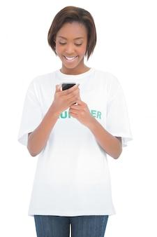 Vrolijke vrijwilligersvrouw die haar mobiele telefoon bekijkt