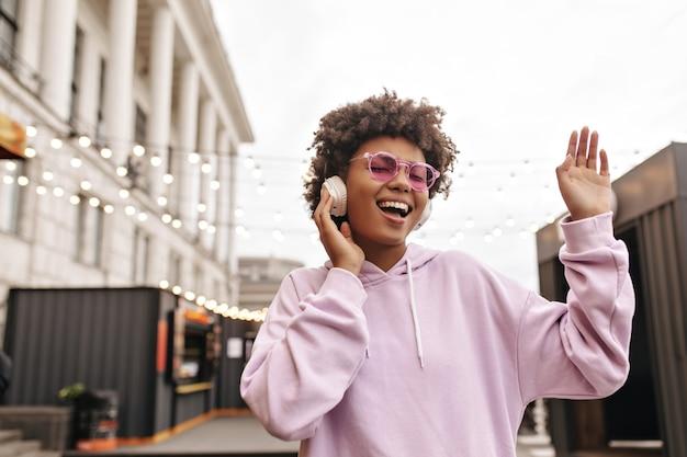 Vrolijke, vrolijke brunette krullende vrouw in hoodie en roze zonnebril luistert naar muziek in een koptelefoon en zingt buiten