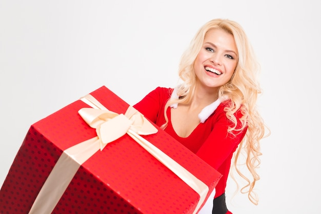 Vrolijke vrolijke jonge vrouw die lacht en een groot rood cadeau vasthoudt