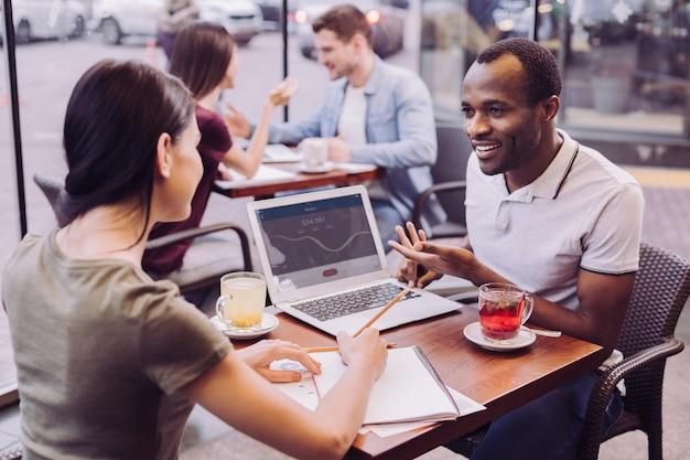 Vrolijke, vrolijke twee collega's die in café werken tijdens het voorbereiden van project en vrouw die ideeën opmerkt