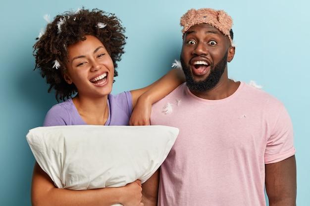 Vrolijke vrolijke zwarte vrouw en man hebben plezier na het slapen, houden kussen vast, hebben veren op het hoofd, glimlachen positief, genieten van rusttijd in de slaapkamer, geïsoleerd over blauwe muur. rust, bedtijd concept