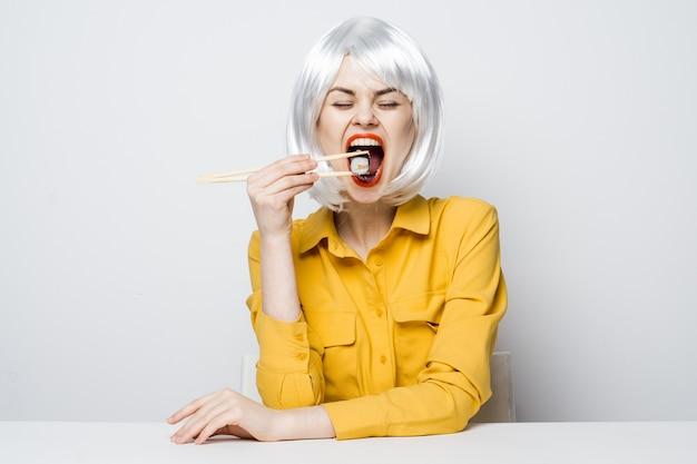 Vrolijke vrouw blonde rode lippen sushi eten