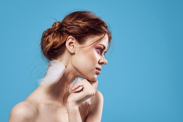 Vrolijke vrouw blote schouders pluizige oorbellen sieraden puur leer blauwe achtergrond.