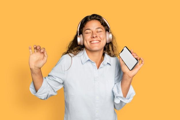 Vrolijke vrouw dansen op muziek met koptelefoon op digitaal apparaat