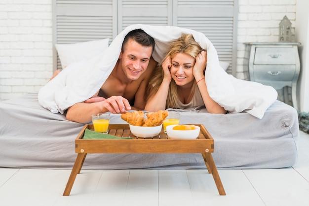 Vrolijke vrouw dichtbij jonge mens in bed onder deken dichtbij voedsel op ontbijtlijst