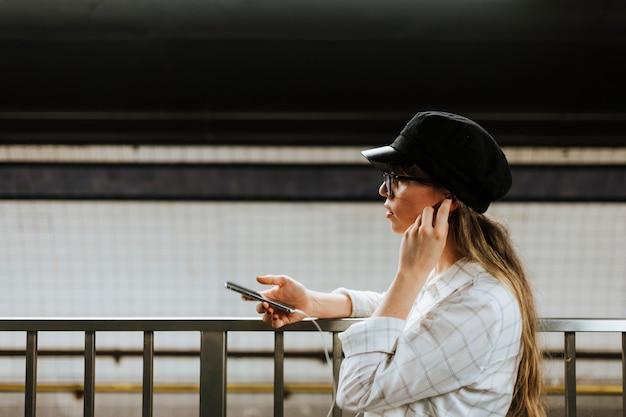 Vrolijke vrouw die aan muziek luisteren terwijl het wachten op een trein bij een metroplatform