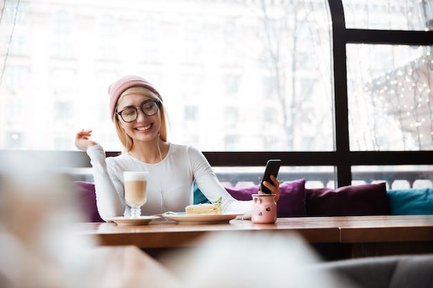 Vrolijke vrouw die aan muziek van celtelefoon luistert in koffie