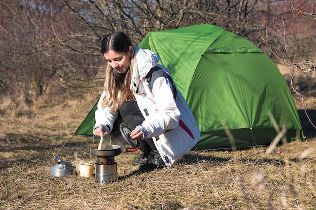 Vrolijke vrouw die alleen het koken voor haar tent kampeert