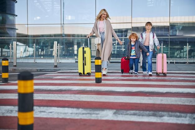 Vrolijke vrouw die de weg oversteekt met kinderen en bagage