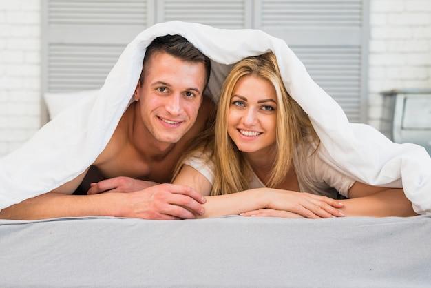 Vrolijke vrouw die dichtbij de jonge glimlachende mens in bed onder deken ligt