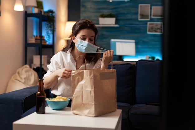 Vrolijke vrouw die een gezichtsmasker voor medische bescherming neemt na het kopen van afhaalmaaltijden