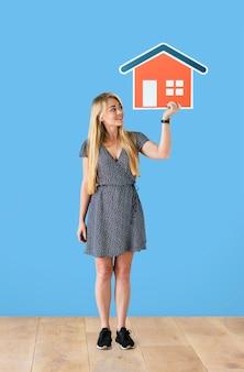 Vrolijke vrouw die een huispictogram houdt