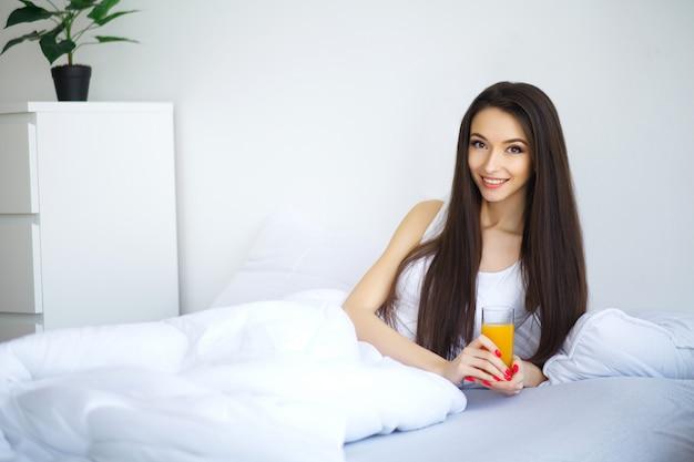 Vrolijke vrouw die een jus d'orangezitting thuis op haar bed drinkt