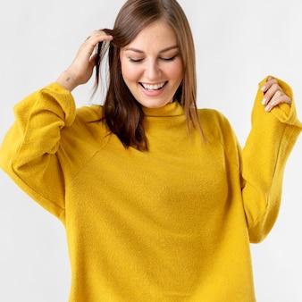 Vrolijke vrouw die een mosterdgele trui draagt