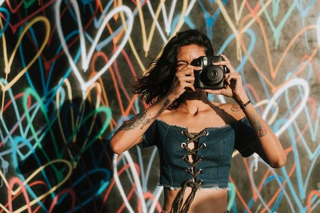 Vrolijke vrouw die een onmiddellijke camera met behulp van