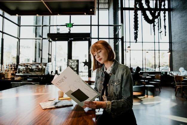 Vrolijke vrouw die een tijdschrift leest in een café