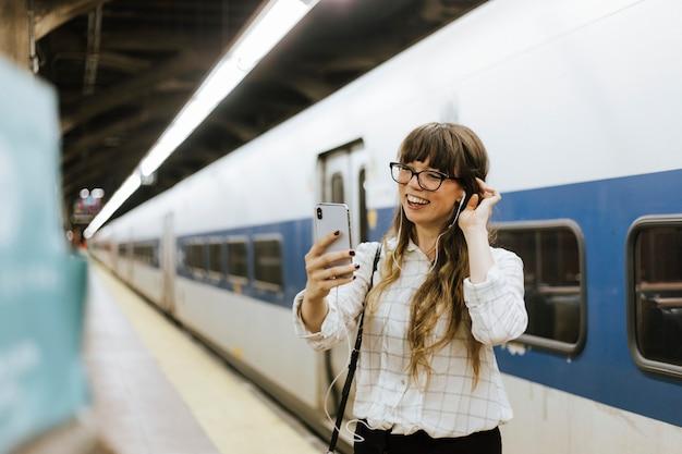 Vrolijke vrouw die een videovraag heeft bij een metroplatform