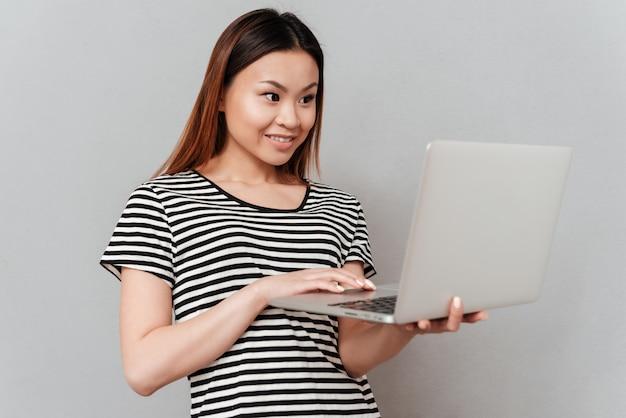 Vrolijke vrouw die geïsoleerde laptop met behulp van