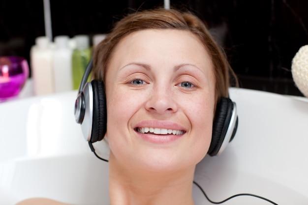 Vrolijke vrouw die hoofdtelefoons in een schuimbad met behulp van