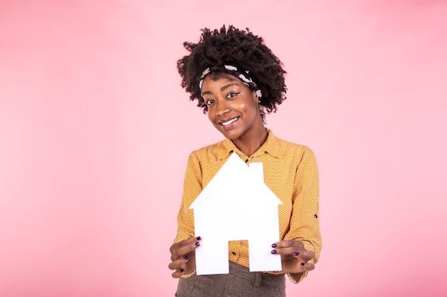Vrolijke vrouw die huis koopt of verkoopt, papieren huis vasthoudt en vrolijk lacht,