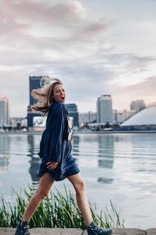 Vrolijke vrouw die in de buurt van de rivier loopt en iets positiefs schreeuwt