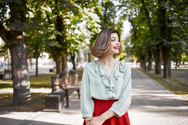 Vrolijke vrouw die in de vrijetijdslevensstijl van parkbomen loopt