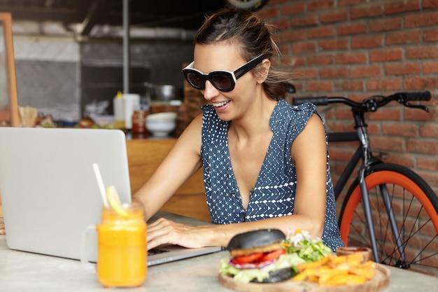 Vrolijke vrouw die in modieuze zonnebril op laptop computer intikken