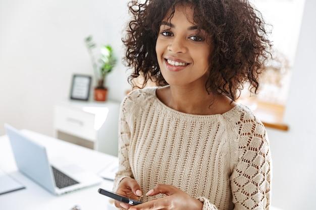 Vrolijke vrouw die in vrijetijdskleding een smartphone draagt en naar de camera kijkt terwijl ze bij de tafel op kantoor staat